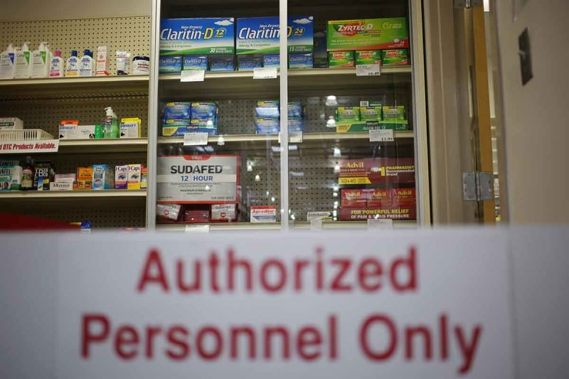 "A sign infront of a shelf of cold medicine reads: ""Authorized Personnel Only"""