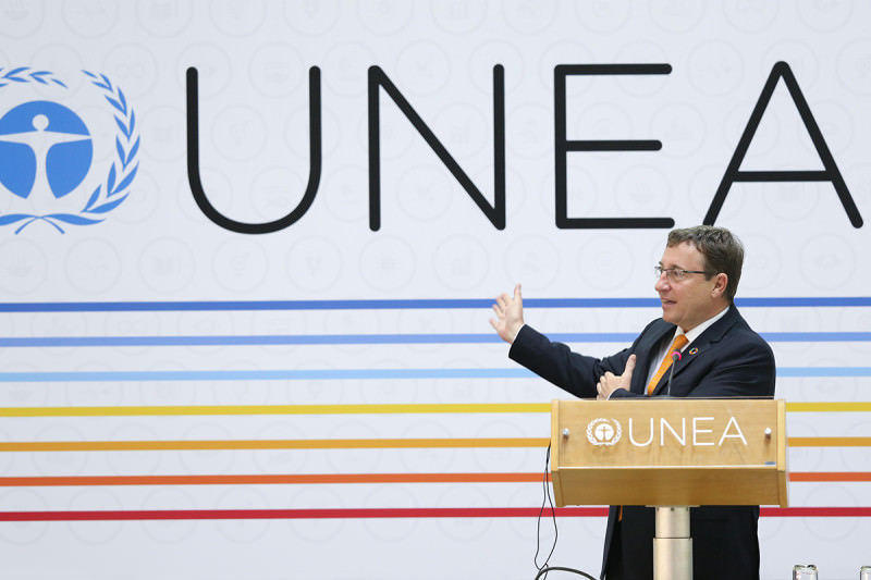 A speaker stand in front of a UNEA banner