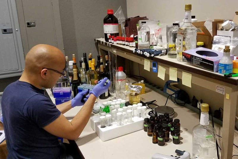 A man wearing gloves sits at a table covered in bottles containing different chemicals