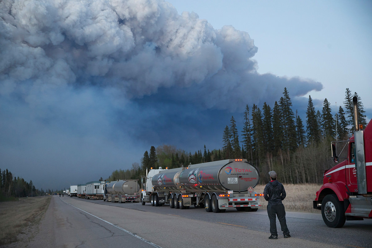 Long line of traffic with massive smoke plume above forest