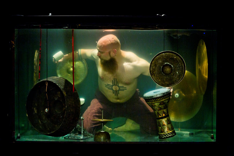 A big guy, barechested with a tattoo, bald head and beard, underwater, playing I think some cymbals
