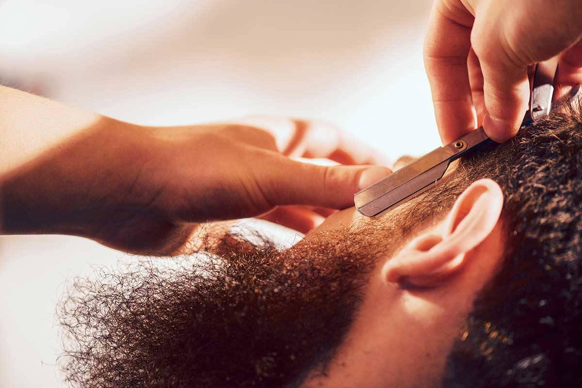 Man having black bushy beard shaved