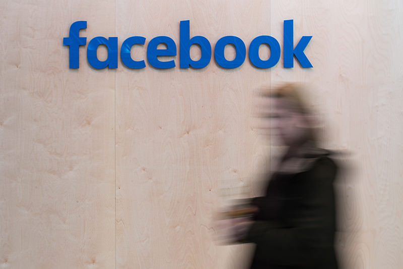 Blurred woman walks in front of Facebook logo