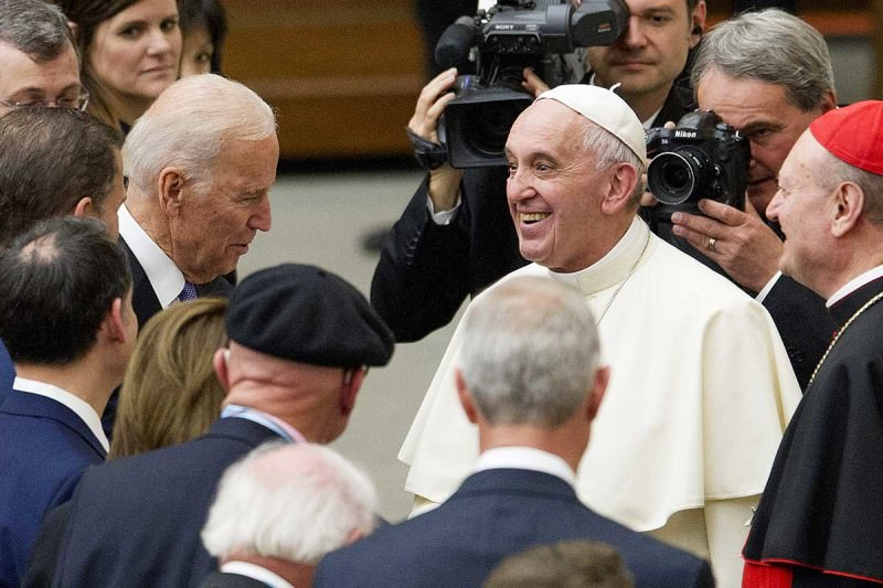 Joe Biden and Pope Francis surrounded by men