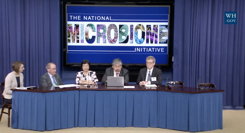 """Panel of five people sitting at a table with a screen behind reading """"The National Microbiome Initiative"""""""