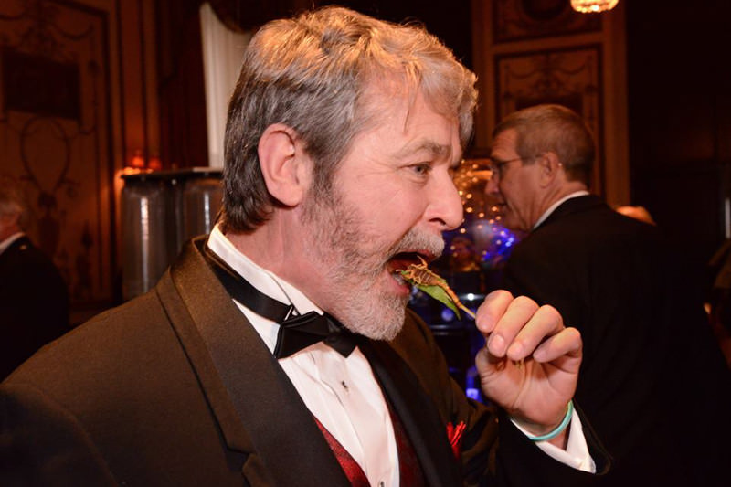A man in black tie eating a scorpion on a stick