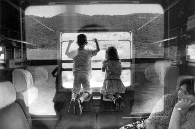 A boy and a girl looking out of a train window