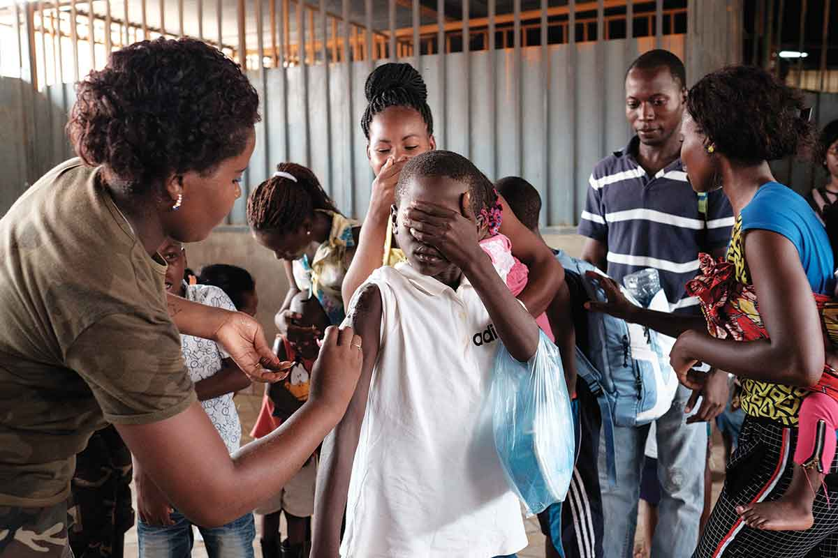 Angolan child covers eyes while being vaccinated