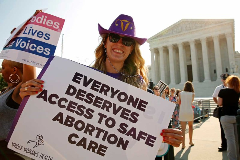 "A smiling woman stand outside the court holding a sign that says ""Everyone deserves access to safe abortion care"""