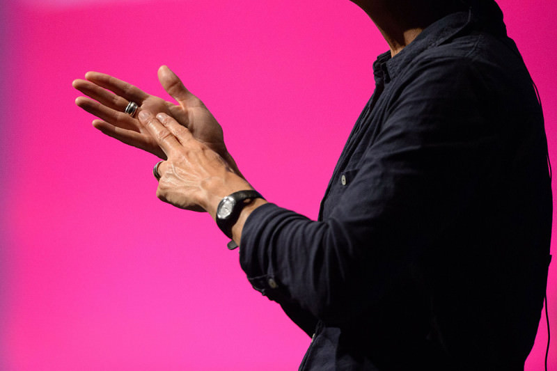"Someone making the British Sign Language gesture for ""N"", against a pink background"