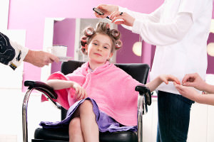 Child in curlers having manicure and hairdo