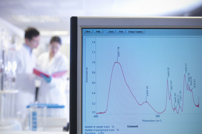 A graph of some results in the foreground with two scientist in lab coats inspecting data in the background