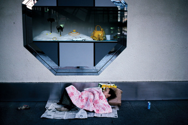 Person sleeping on pavement underneath luxury items window display