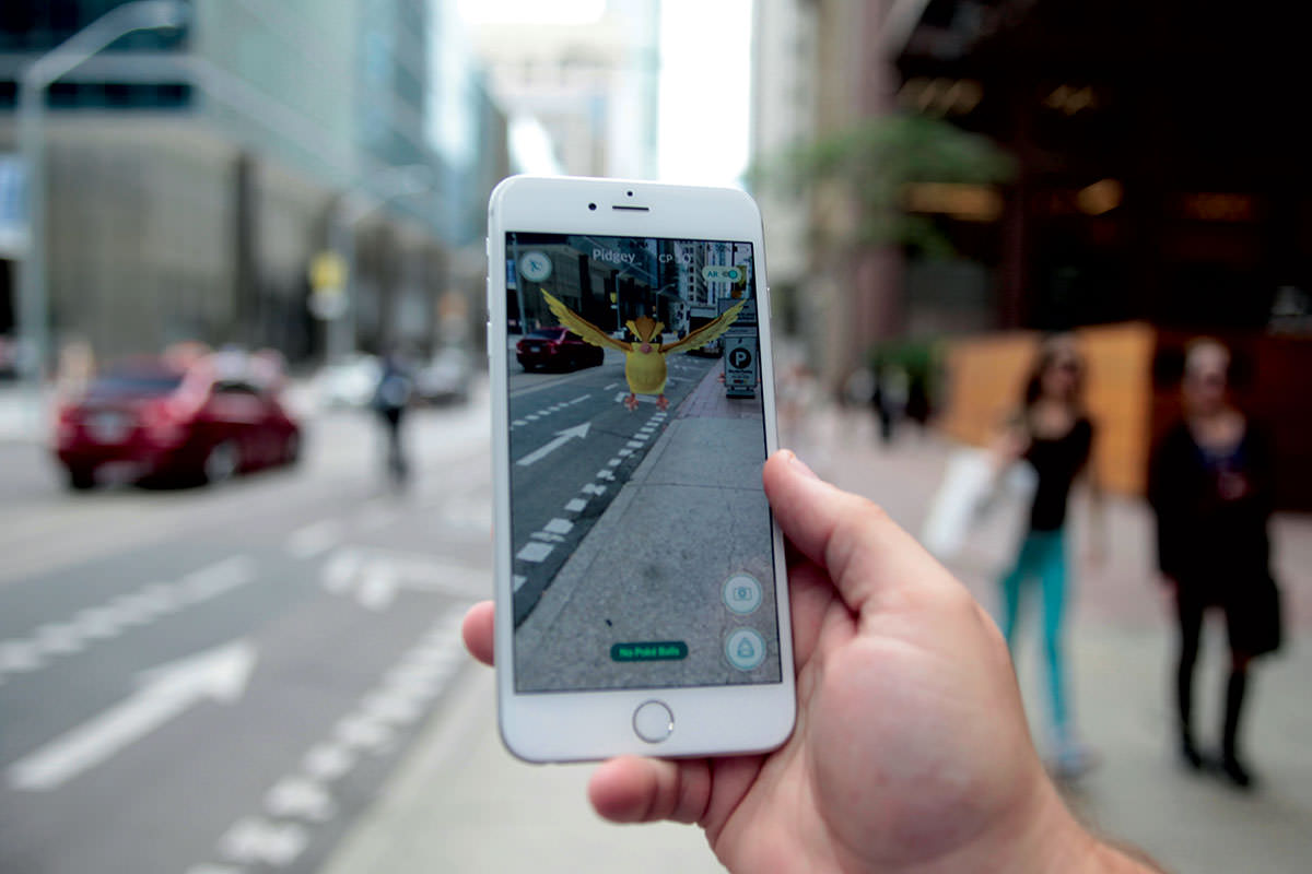 Smartphone being held up showing augmented reality version of street, with Pokémon added