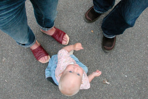 A toddler looking up with two adults' feet in the shot