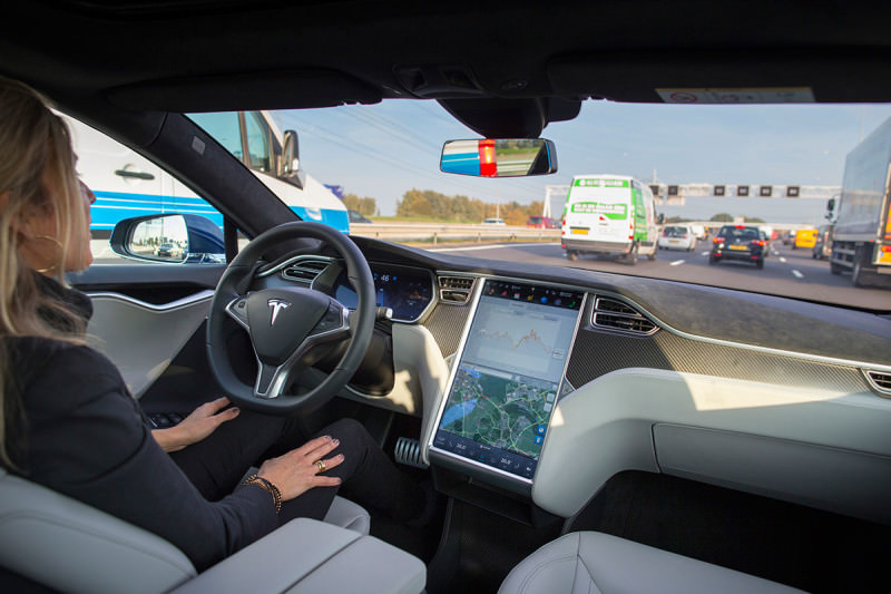 A woman sits in the driver's seat of her Tesla car, driving down a road without her hands on the steering wheel