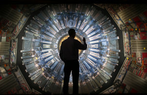 A visitor takes a phone photograph of a large back lit image of the Large Hadron Collider (LHC) at the Science Museum's 'Collider' exhibition on November 12, 2013 in London, England
