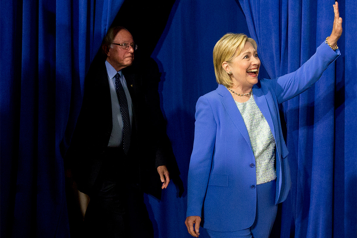 Clinton waves in front of a stage curtain while Sanders emerges from the wings behind her