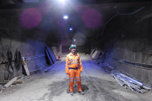 A man wearing an orange boiler suit, hard hat and headtorch stands in the mine