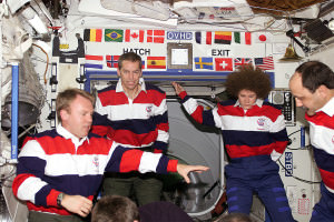 Astronauts on the International Space Station with many flags on panel behind them