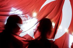 Two people silhouetted against the Turkish flag