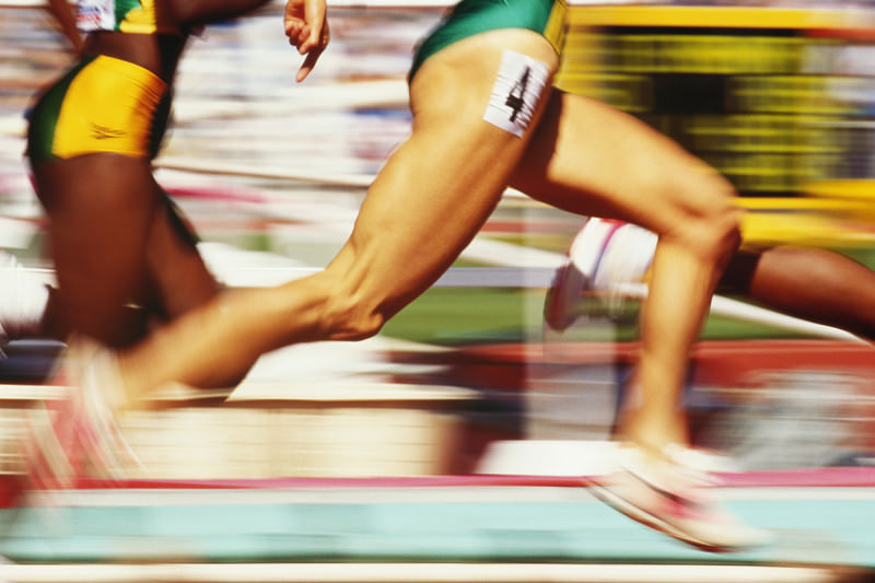 Female athletes running in race, close-up on legs,blurred