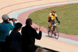 older man riding a bike around an outside track