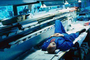 A man sleeps in an artificially lit factory