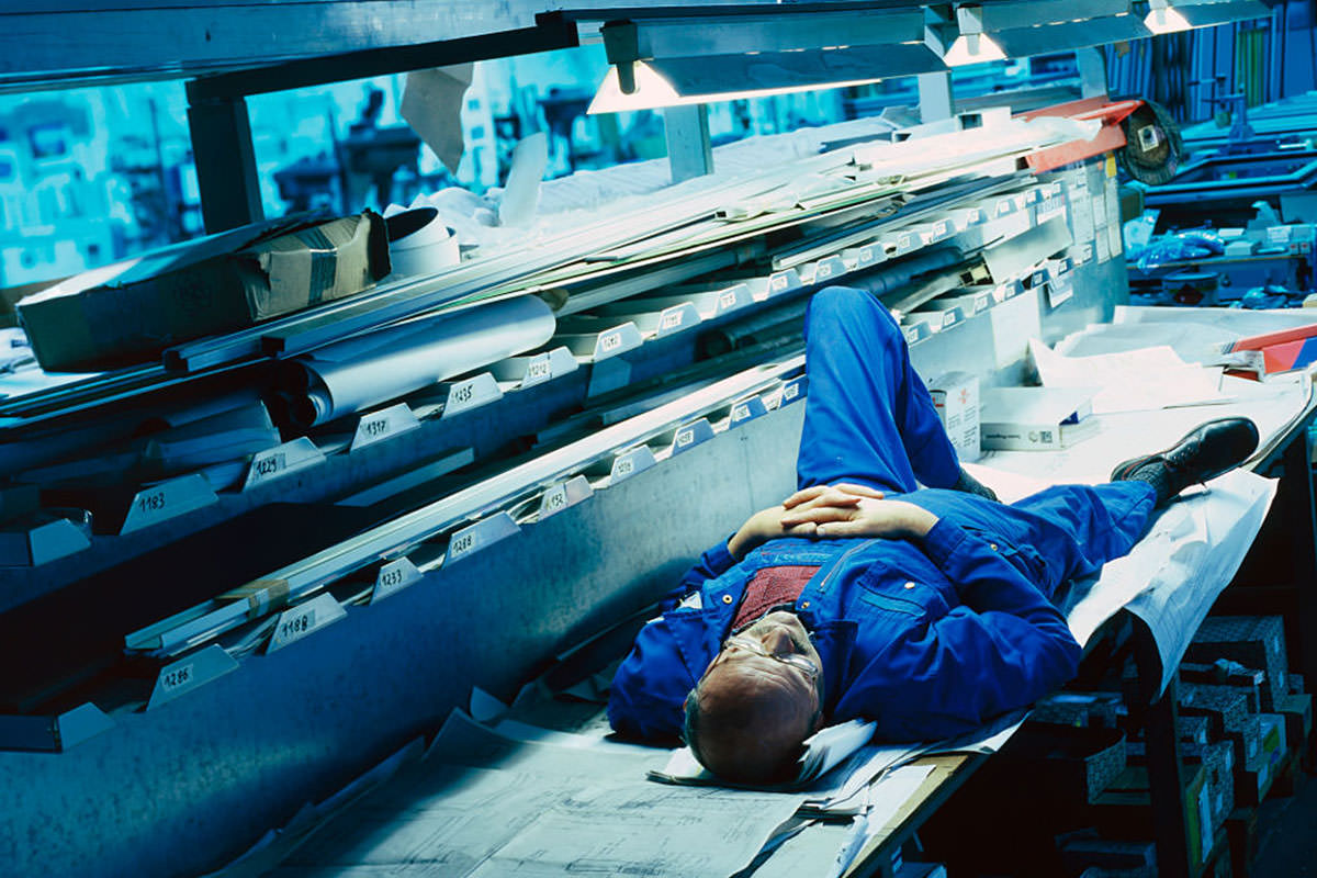 A man sleeps in an artificially lit factory