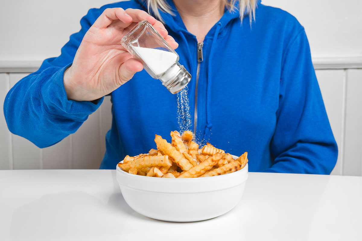 A woman adds salt to her chips