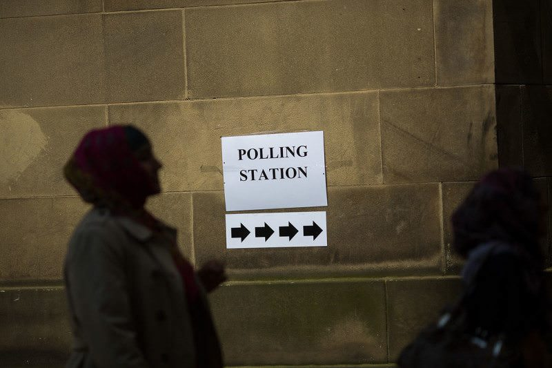 silhouette of a person next to a sign pointing the way to a polling station