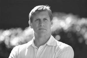 Zoltan Istvan, head and shoulders, pictured in black and white with clouds in the background. He's white, square-jawed and arrogant-looking