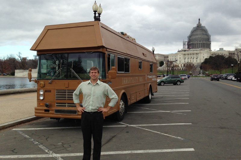 "Istvan standing, hands on hips, in front of his ""Immortality Bus"" which is brown and done out to look like a coffin. It looks as lame as you might imagine, especially since it's in front of the impressive Capitol Hill building"