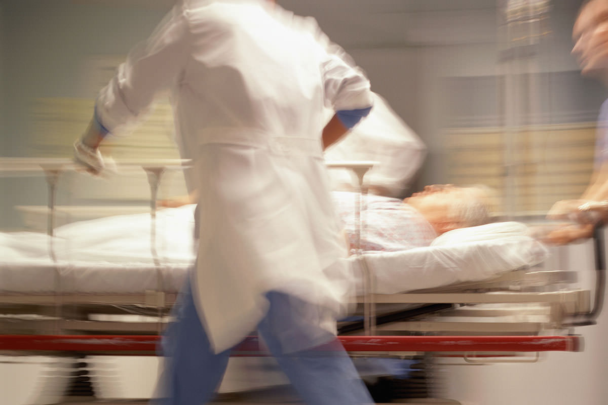 A person in a bed being pushed through hospital