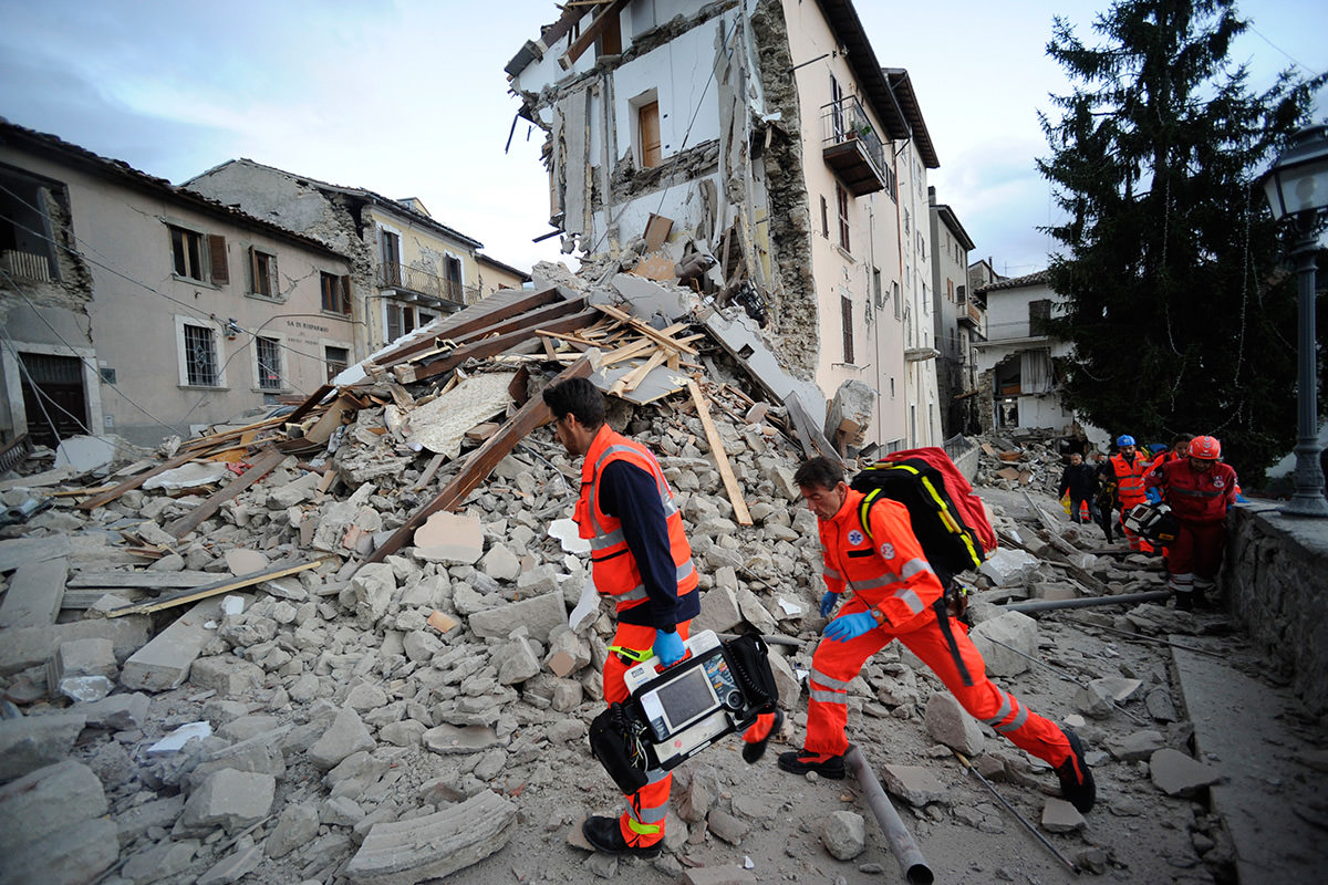 Rescuers search a crumbled building in Arcuata del Tronto