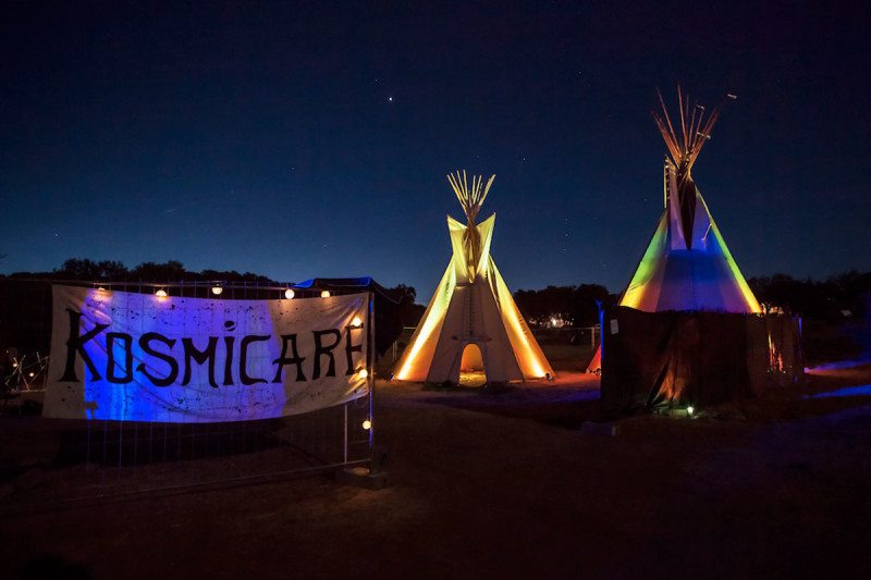 Kosmicare banner and teepees at night