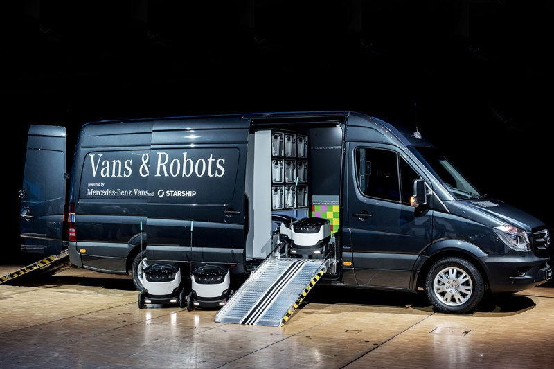 A van with its side door open revealing small robots inside