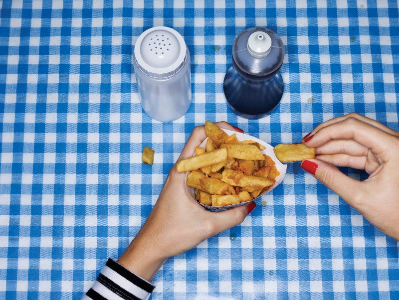 Hands holding a carton of chips on a tablecloth