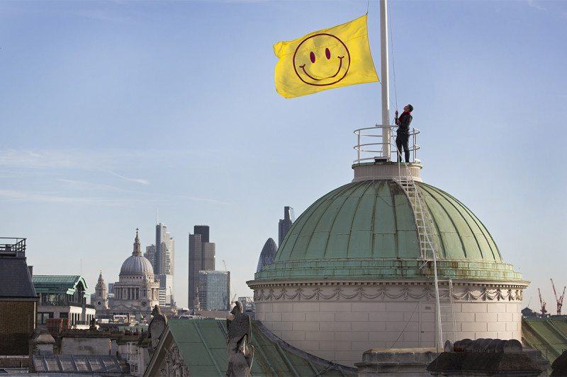 Person raising yellow flag with smiley face on it above dome with London skyline including St Paul's Cathedral in the background