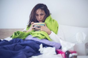Woman in bed looking ill with cold or flu