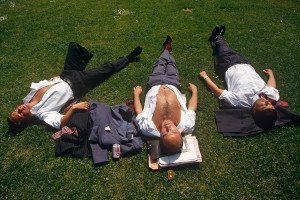3 people napping outside on the grass