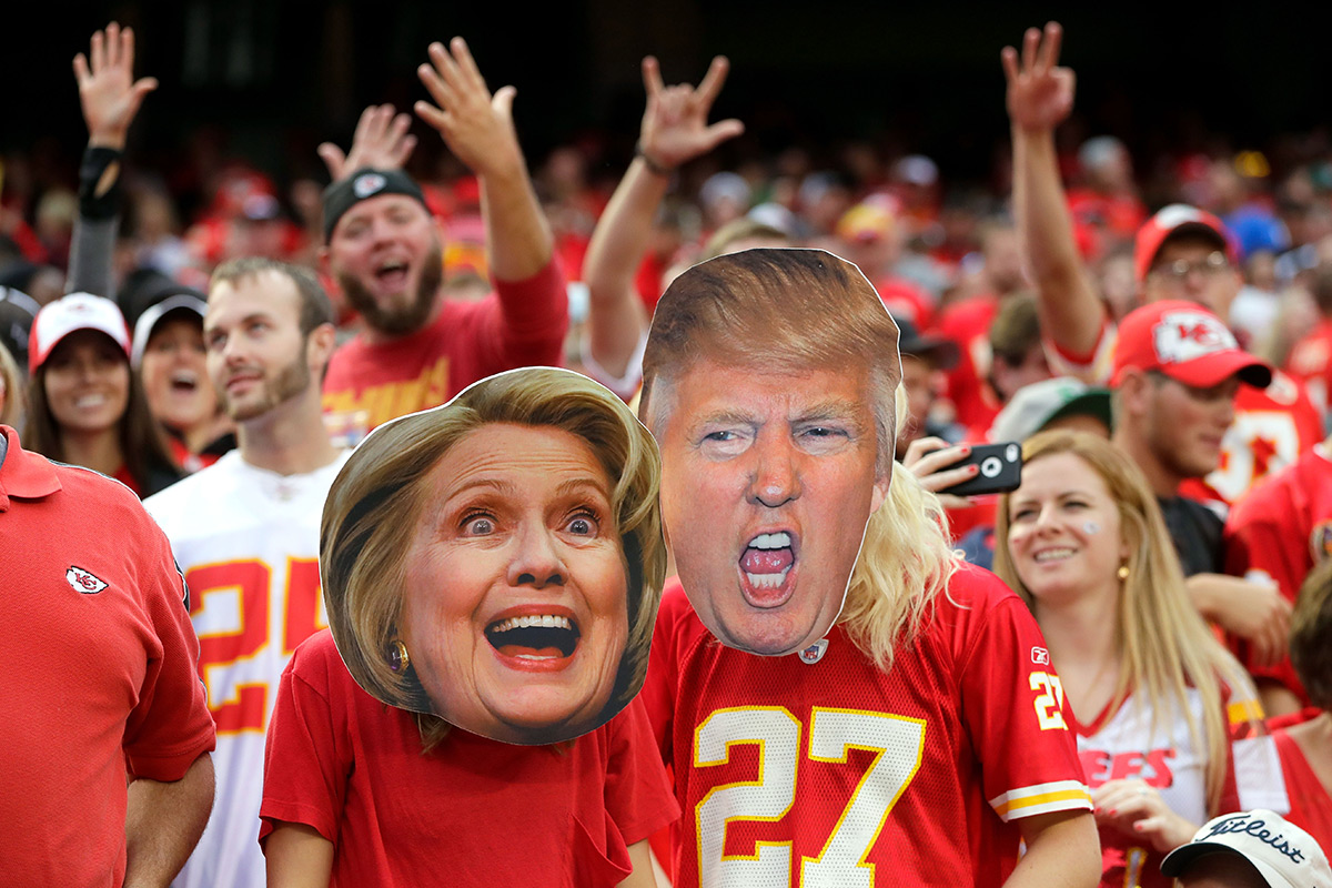 People at rally wearing Clinton and Trump masks