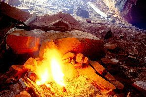A fire burns in a stone hearth in a cave