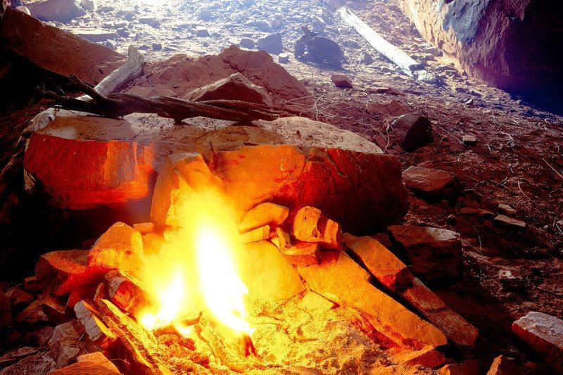 Un feu brûle dans un foyer en pierre dans une grotte