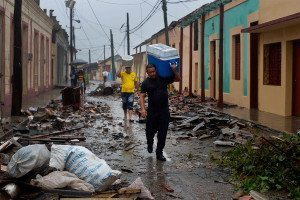 Residents carry food down a street strewn with rubble caused by Hurricane Matthew in Baracoa, Cuba, Wednesday, Oct. 5, 2016. The hurricane rolled across the sparsely populated tip of Cuba overnight, destroying dozens of homes in Cuba's easternmost city, Baracoa, leaving hundreds of others damaged