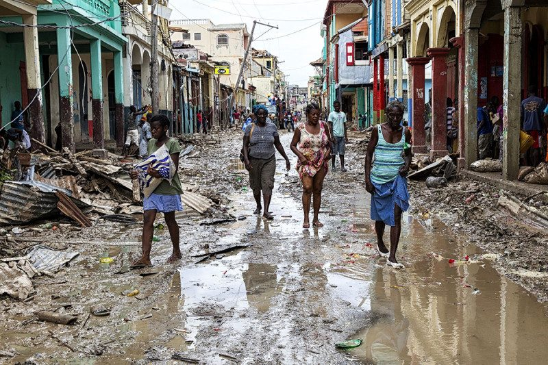 People walk down a flooded street in Haiti