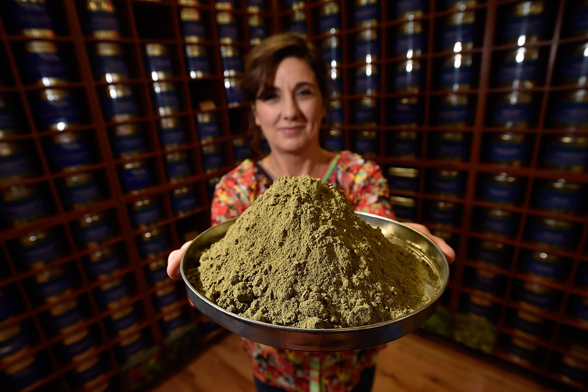 Woman holds platter of brown powder