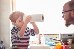 Man speaks to child who is looking down the centre of a roll of kitchen paper