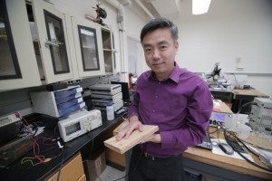 Xudong Wang holds a piece of his energy-generating board in a lab