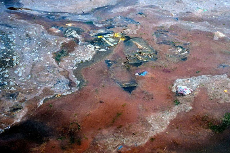 Dirty, red-tinged water with scum and rubbish floating on the surface